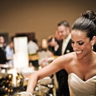 A bride smiles as she serves herself some delicious food off of a buffet. Additional guests can be seen behind her.