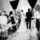 A bride walks down the aisle with a man. Guests line the aisle and stand as she walks by.