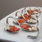 Diced tomatoes and other cheese are presented on decorative spoons.