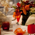 A close up of orange and red flowers on a set table. Candles are next to the flowers, along with plates and water glasses.