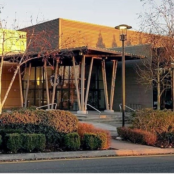 front entrance of the Lynnwood Convention center is the orange dusk sky