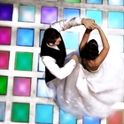 A bridge and groom dance on a pixelated floor.