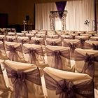 Chairs covered in individual white covers, complete with a purple bow, face a stage dressed for a wedding.