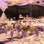 Set tables look toward a stage. Drapes fall from the ceiling/ Black drapes hang from the wall.