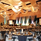 Set tables look towards a brightly lit stage. Drapes swing from the ceiling, and projection screens flank the stage.