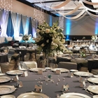 A vase of white flowers is surrounded by plates. Tables stretch out into the room. Blue lights dance up the wall.