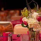 A close up of the flowers on a table. The flowers are mostly white and the tablecloth is a brilliant pinkish red.
