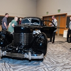 An old fashioned black car is looked at by a group of people. The car is in a large room.