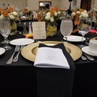 A table is set with plates, utensils, glasses and black napkins. Orange and white flower arrangements decorate the table.