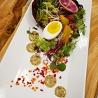 A salad is prepared across a long plate. A hard boiled egg is in the middle of the salad.