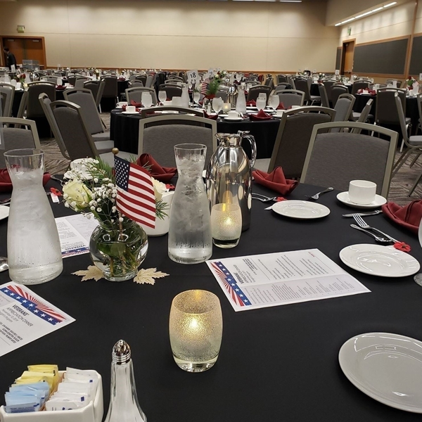 Table setting with a red and white rose centerpiece and an American flag.