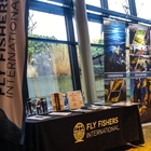 A booth is set up against floor to ceiling windows. The booth is for fly fishers international.