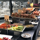A delicious looking buffet is spread out. The buffet includes grapes, a vegetable tray and sandwiches.