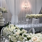 Wedding decorations cover a room. White flowers adorn the table, while a white cake is also viable.