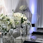 A table is set with white flowers in glass vases. White wall drapes are seen in the background.