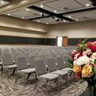 A large room has multiple rows of chairs. A vase of flowers faces the rows of chairs.