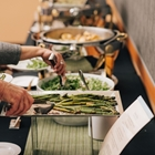 Two people go down a buffet line. One person reaches for the asparagus, another for a salad.