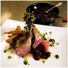 Lamb chops are presented on a plate. They look yummy.