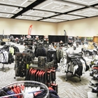 A large room is filled with various clothing apparel. Most of it is motorcycle related.