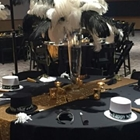 A close shot of a New Years themed table. A large feathered centerpiece stands on the table. Bowler hats surround the table.