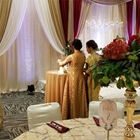 Two guests stand near a small round table to examine the flowers. Beautiful white, gold and red curtains cover the wall.