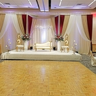 A stage stands in front of a dance floor. A white couch is flanked by two chairs and vases full of beautiful flowers.