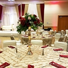Tables look towards a stage with a white sofa. The table is set with utensils and red napkins.