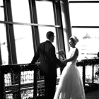 A bride and groom look into each others eyes in front of floor to ceiling windows.