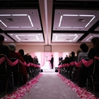 A path lined with rose petals leads to a bride and groom. Guests sit to the left and the right of the path.