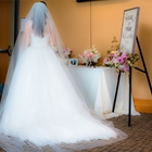 A bride looks away from the camera. She stands next to a table covered in flowers and an announcement board.