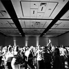 Multiple people dance in this black and white photo.
