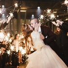 A bride and groom kiss as guests wave sparklers.
