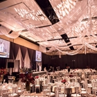 A large room is filled with white tables and chairs. Red flowers are on each table. White draperies cover the ceiling.