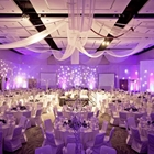 Tables and chairs draped in white cloth face toward a stage. Brilliant lights surround the room.