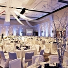 Multiple tables and chairs are covered in white cloth. White drapes hang from the walls and ceiling. Lights sparkle on the walls.