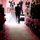 A bride walks down the aisle as the guests stand up. Six men stand at the end of the aisle.
