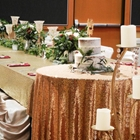 A long table, set with utensils and flowers, is next to a small round table. The round table has a layered cake.