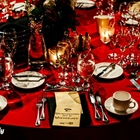 A red table has been set for dinner. Plates, menus, and glasses are on the table.