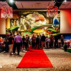 A red carpet leads to a social gathering of many people. A large painting hangs on the wall, while red light flanks the side.