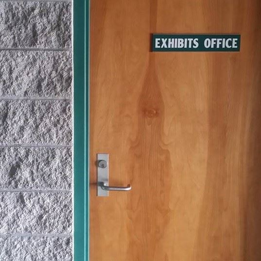 "Wooden door with Green trim that says ""Exhibits Office"""
