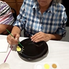 A lady painting yellow flowers on a black plate