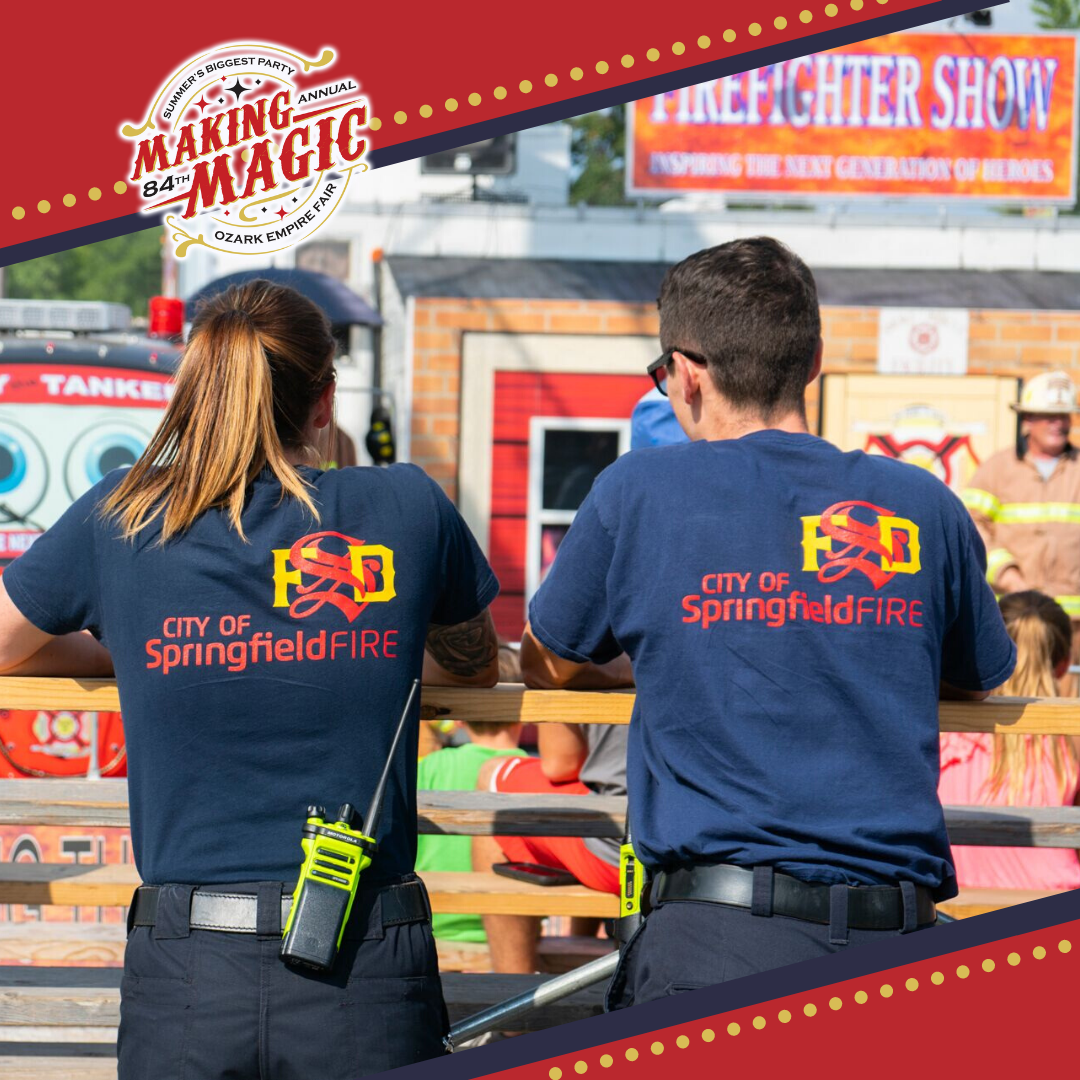 Two Springfield Fire Fighters watching an outside kids fire fighter show