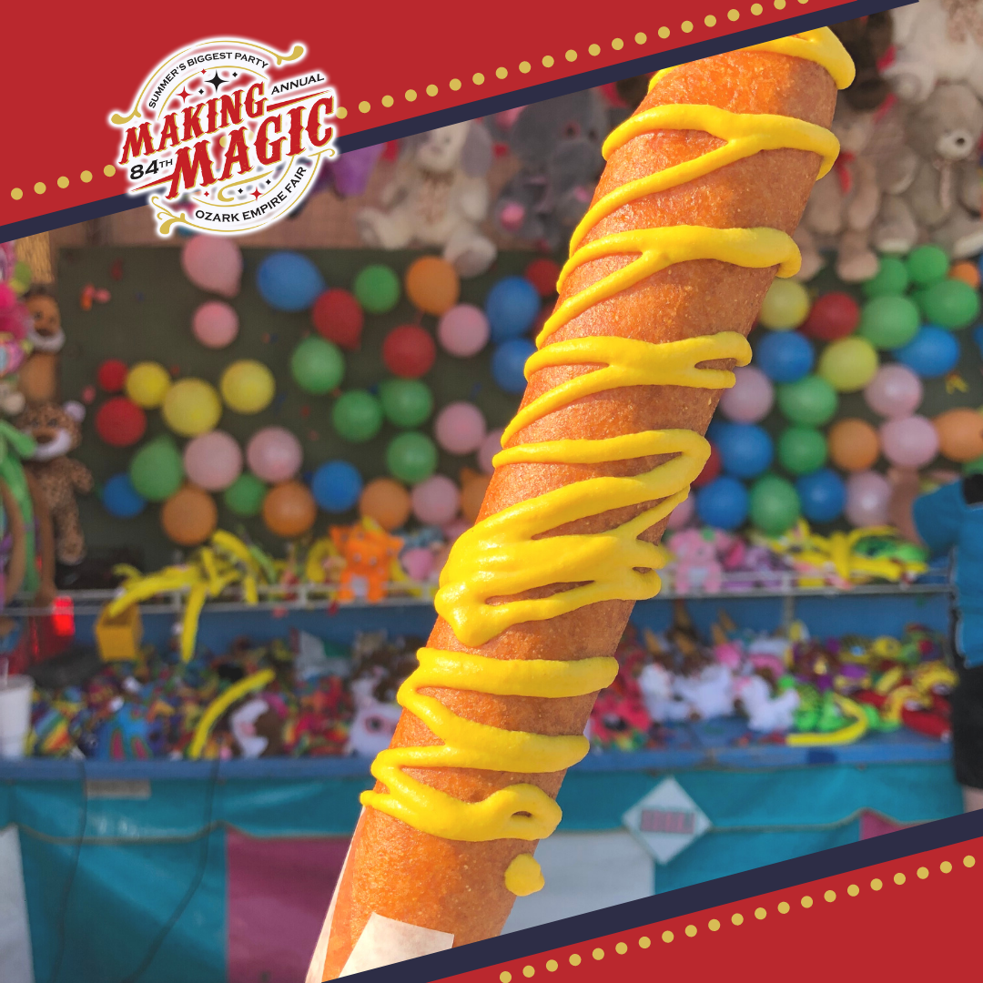 Foot long corn dog with mustard drizzled over it.