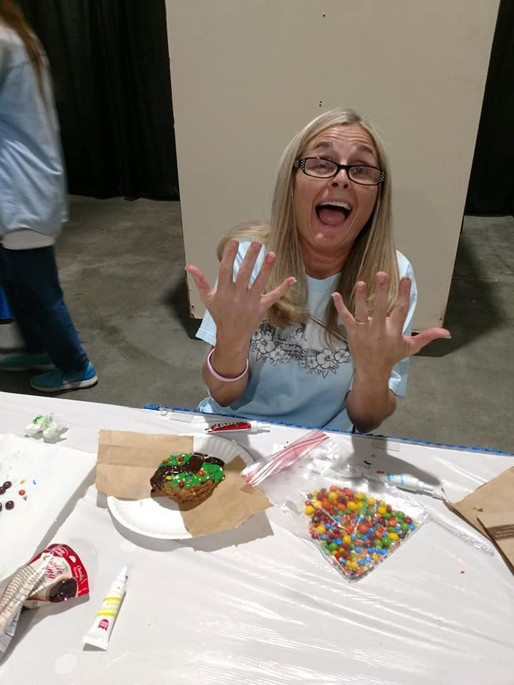 Lady with her hand covered in frosting from decorating cookies at our life & arts exhibits during the Ozark Empire Fair
