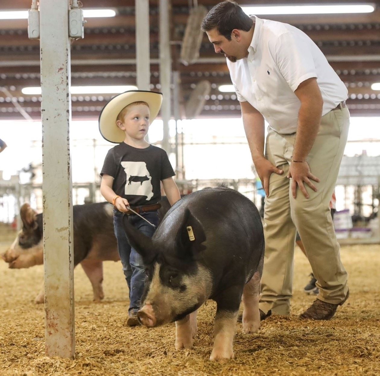 Young boy showing a pig in an arena while a judge asks him a question.