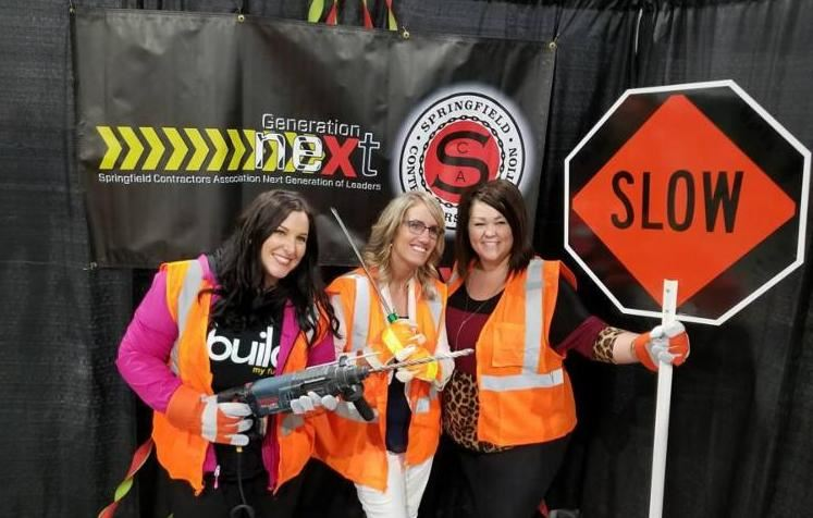 Three ladies wearing construction orange vests with various construction signs.