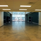 Center Hall Entrance with a women's restroom on the left and a men's restroom on the right. White walls and concrete floors