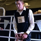 A young man positions his goat in the show ring