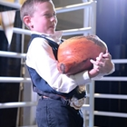 A young man proudly displays his cured ham in the show ring