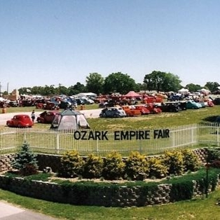 "Retro image of the main white gate at our facility that says ""Ozark Empire Fair"" on it"